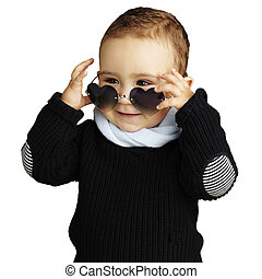 portrait of funny kid wearing heart sunglasses against a...