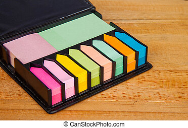 Multicolored post it note block in black leather case on...