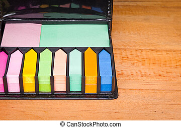 Multicolored post it note block in black leather case -...