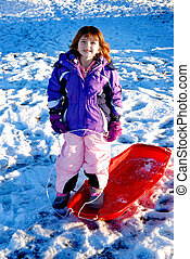 Sledding - Little girl sledding in winter snow