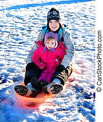 Sledding - Little girl sledding in winter snow