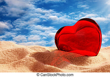 Red glass heart in sand