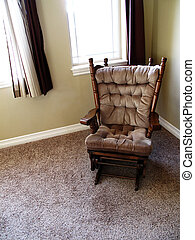 Rocking chair in home next to large windows