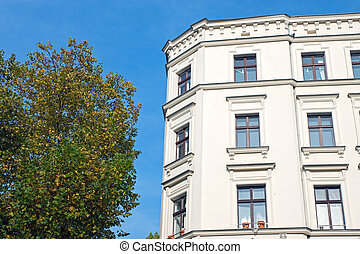 Green tree and white town house in Berlin