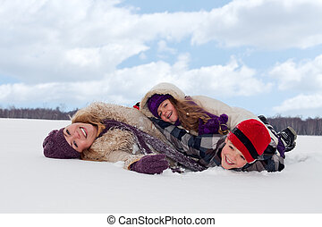 Family having fun in the snow on a winter day