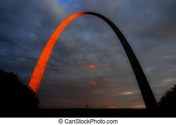 Runner running under the glowing St. Louis Arch at sunset