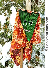 Funny broom with an ugly face in winter