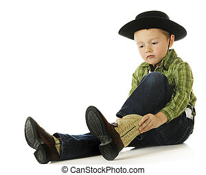 Cowboy Getting Booted - A cute preschool cowboy putting on...