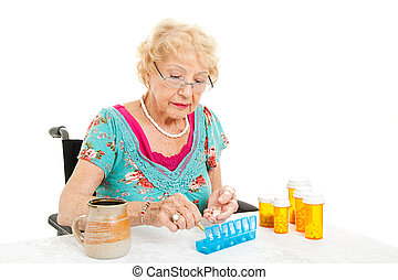Woman In Wheelchair Counts Pills - Senior woman in a...