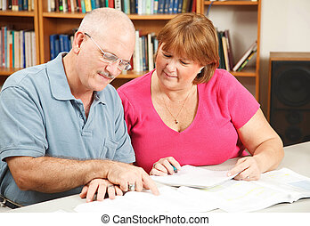 Adult Education Couple - Adult students studying together in...