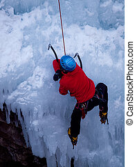 Ice Climbing - Alpinist ascenting a frozen waterfall in Ice...