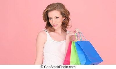 Excited Woman Shopper clutching a red, green and blue paper...