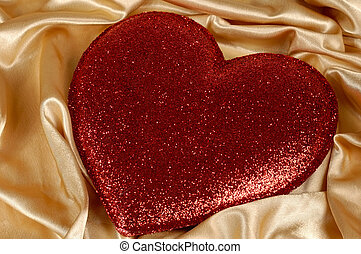 Red valentine on gold fabric background - Red heart-shaped...