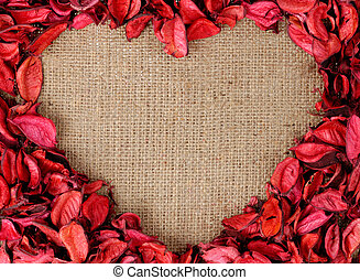 Heart shaped frame made by red petals