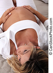 pregnant blonde woman elongated on a bed is touching her stomach