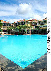 The swimming pool at luxury hotel and outdoor restaurant by...