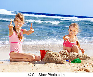 Kids playing on beach. - Thumb up children playing on beach....