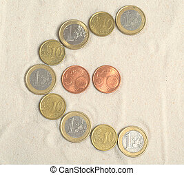 Symbol of euro with euro coins on the sand