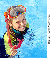 Child in swimming pool learning snorkeling. Sport.