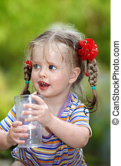 Child drink glass water. Outdoor.