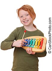 Girl plays xylophone - Portrait of a young girl playing a...