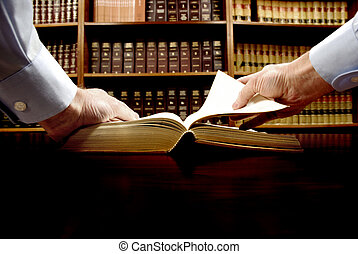 Hand on Book - Hands holding an old book with library in...