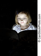 Litte Girl Reading at Night - Little girl reading book in...