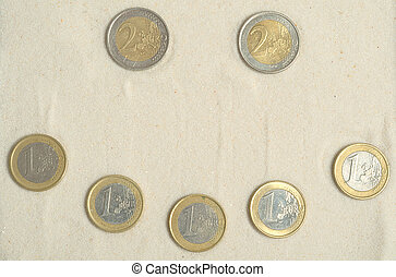 Symbol of smile made of euro coins on the sand