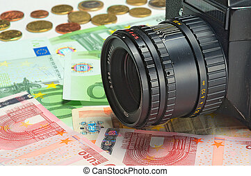 Photocamera lying on the euros for background