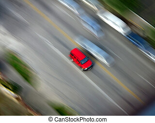 Driving - Red Car driving along road with blurred background