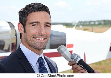 Journalist next to plane