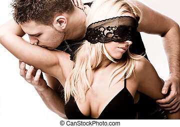 intimate moments - young masked couple in love, studio shot...