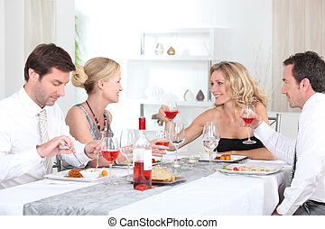 Two couples enjoying meal together