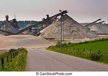 sand mining site with acces road and blue sky