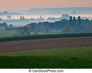 View over hazy agricultural landscape in the early morning -...