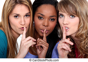 Three women with the fingers to their lips