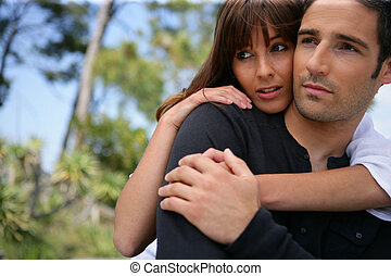 Serious couple embracing in a park