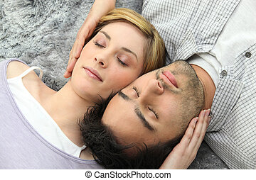 Couple sleeping on gray carpet