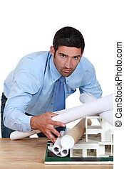 young architect bending over desk with blueprints and model