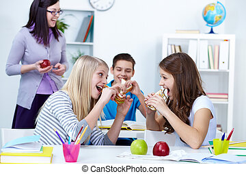 Hungry students - Hungry girls eating sandwiches during...