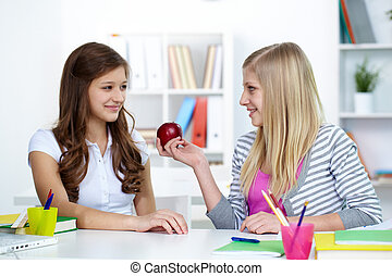Kindness - Cute girl offering her friend an apple during...