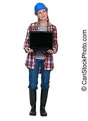Pensive female builder holding laptop