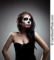 Young woman in day of the dead mask skull face art - Serious...