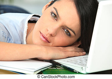 Girl falling asleep next to laptop computer