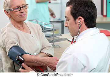 Doctor checking the blood pressure of an elderly lady