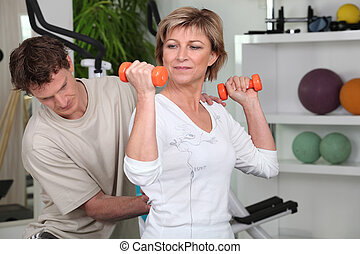 Mature woman working out with dumbbells and a personal trainer