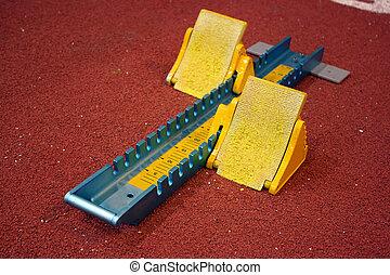 Athletic start block on dark red tartan track