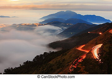 beautiful sea of cloud with mountain with car light trail