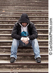 Sad teenage boy with hood sitting on stairs