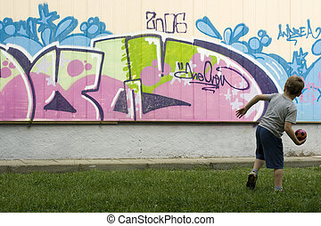 Child plays with the ball in the park with graffiti painted...